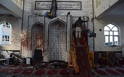 An armed Afghan civilian looks inside the Imam Zaman Shiite mosque which was a the site of a suicide attack during evening prayers, in Kabul on October 21, 2017 (AFP/WAKIL KOHSAR)