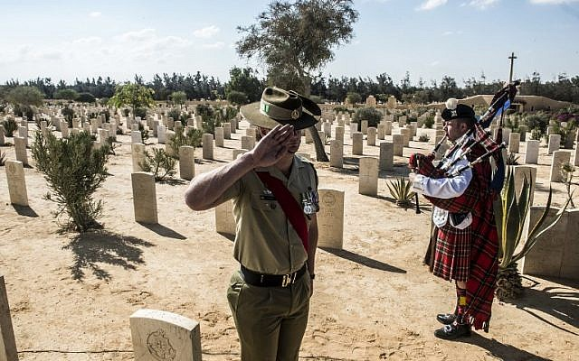 Australian Army Recruit Instructor (RI) Chris Purdie salutes a grave gives a salute before a grave during a ceremony to mark 75 years since the pivotal WWII battle in the town of El Alamein, about 100 kilometers (62 miles) west of Alexandria, during a visit by Egyptian President Abdel Fattah el-Sissi, on October 21, 2017. (AFP PHOTO / KHALED DESOUKI)