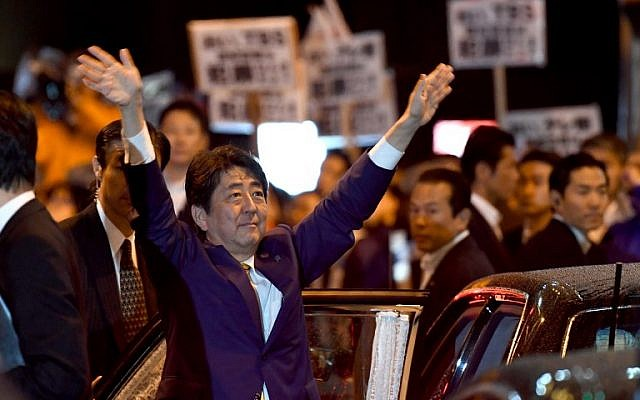 Japan's Prime Minister and ruling Liberal Democratic Party leader Shinzo Abe waves to his supporters in Tokyo while leaving his last stumping speech ahead of the October 22 general election, on October 21, 2017. (AFP Photo/Toshifumi Kitamura)