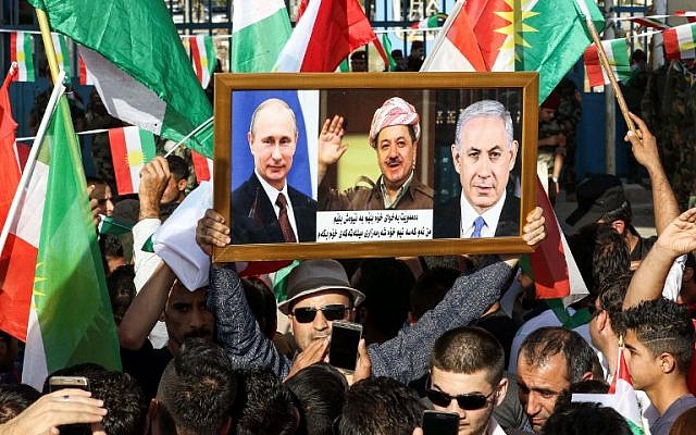 An Iraqi Kurdish man holds a picture frame with portraits of Russian President Vladimir Putin (L), Israeli Prime Minister Benjamin Netanyahu (R), and Iraqi Kurdistan President Massoud Barzani during a demonstration outside the UN Office in Irbil, the capital of the autonomous region, on October 21, 2017. (AFP Photo/Safin Hamed)