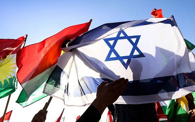 A picture taken on October 21, 2017, shows a man holding an Israeli flag alongside the flag of Iraqi Kurdistan during a demonstration outside the UN Office in Irbil, the capital of the autonomous region. (AFP Photo/Safin Hamed)