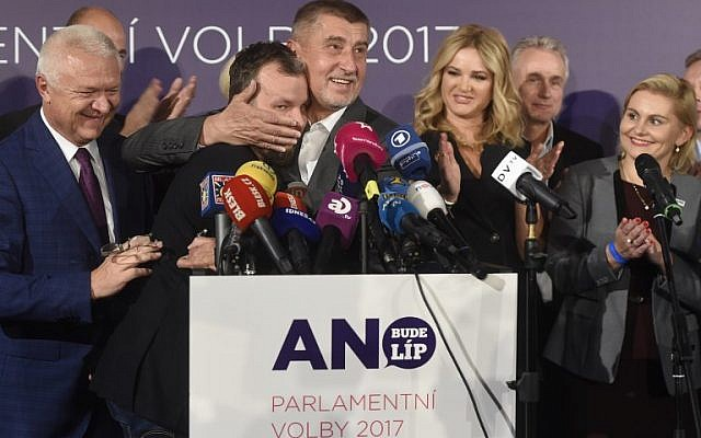 Czech billionaire Andrej Babis (C,R), chairman of the ANO movement (YES) kisses Marek Prchal, PR manager of ANO for social media at ANO headquarter after Czech elections on October 21, 2017 in Prague. (Michal Cizek/AFP)