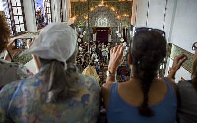 "Moroccan Jews and Israeli Jewish tourists participate in Simchat Torah festivities at a synagogue in the ""Mellah"" Jewish quarter of the Medina in Marrakesh on October 13, 2017.. (AFP PHOTO / FADEL SENNA)"