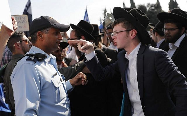 An ultra-Orthodox Jewish demonstrator points towards at a policeman during a demonstration against the conscription of ultra-Orthodox Jews community to the IDF outside the Knesset in Jerusalem on October 23, 2017. (AFP Photo/Thomas Coex)