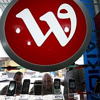 This file photo taken on October 14, 2009, shows Palestinian men looking at mobile phones displayed under the logo of the Palestine phone company Wataniya, at a shop in the West Bank city of Jenin. (AFP Photo/Saif Dahlah)