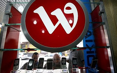 Palestinian men looking at mobile phones displayed under the logo of the Palestine phone company Wataniya, at a shop in the West Bank city of Jenin, on October 14, 2009. (AFP Photo/Saif Dahlah/File)