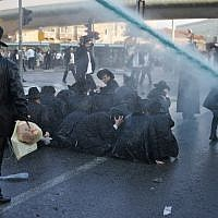 Police spray water to try and disperse a protest by ultra-Orthodox Jews against the conscription of members of their community to the IDF at the entrance to Jerusalem on October 23, 2017. (AFP Photo/Ahmad Gharabli)
