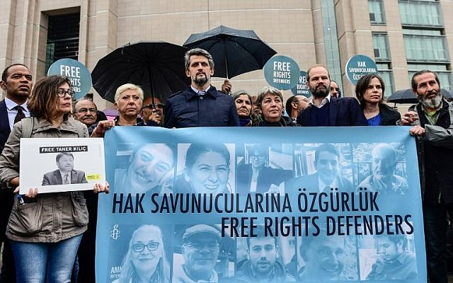 "John Dalhuisen Amnesty International's Europe Director (3rd L) joins protesters as they hold a banner that reads, ""Free rights defenders"" during a rally outside the court house where the trial of eleven human rights activists is taking place in Istanbul, on October 25, 2017. (AFP PHOTO / YASIN AKGUL)"