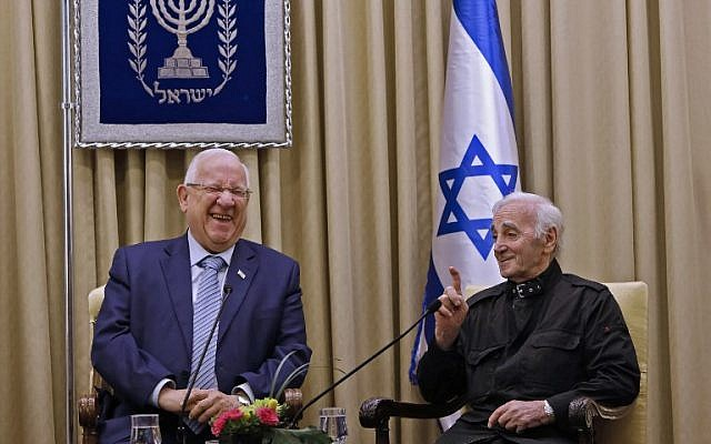 President Reuven Rivlin is seen with French-Armenian singer Charles Aznavour on October 26, 2017, at the President's Residence in Jerusalem. (AFP Photo/Gali Tibbon)