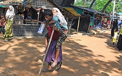 A Rohingya refugee carries an elderly woman toward a makeshift shelter at Kutupalong refugee camp in the Bangladeshi district of Ukhia, October 26, 2017. (AFP/Tauseef MUSTAFA)