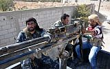 Syrian soldiers and pro-regime militiamen man a heavy machine-gun mounted on the back of a pickup truck as they ride in the recently retaken desert town of Al-Qaryatain on October 26, 2017. (AFP Photo/Stringer)