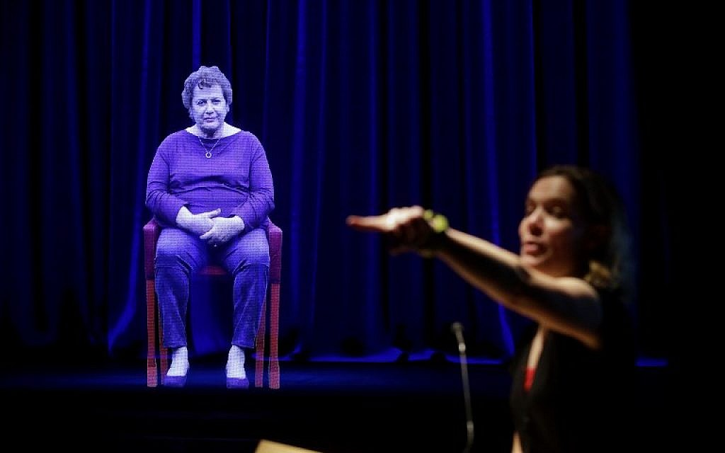 Amanda Friedeman takes a question from a student directed to Holocaust survivor Adina Sella, as she is displayed as a three-dimensional hologram at the Take A Stand Center in the Illinois Holocaust Museum and Education Center on October 26, 2017, in Skokie, Illinois. (Joshua Lott/AFP)
