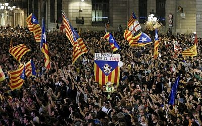 "A flag with the text in Catalan ""The people lead"" is held up as people gather to celebrate the proclamation of a Catalan republic at the Sant Jaume square in Barcelona on October 27, 2017. (AFP/PAU BARRENA)"