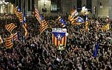 "A flag with the text in Catalan ""The people lead"" is held up as people gather to celebrate the proclamation of a Catalan republic at the Sant Jaume square in Barcelona on October 27, 2017. (AFP PHOTO / PAU BARRENA)"