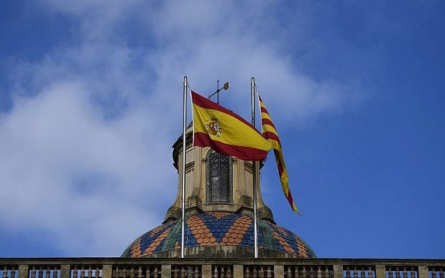 The Spanish (L) and Catalan Senyera flags flutter over Catalonia's Generalitat Palace in Barcelona on October 28, 2017, a day after direct control was imposed on the region over a bid to break away from Spain. (AFP PHOTO / PIERRE-PHILIPPE MARCOU)