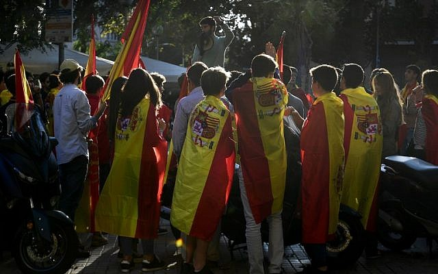 A young man uses a megaphone as other youths wrapped in Spanish flags listen to him  during a demonstration calling for unity in Barcelona on October 28, 2017, a day after direct control was imposed on Catalonia over a bid to break away from Spain.(AFP/PIERRE-PHILIPPE MARCOU)