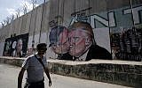 A tourist walks past a graffiti by street artist Lushsux, depicting US President Donald Trump kissing Israeli Prime Minister Benjamin Netanyahu drawn on the security barrier separating the West Bank town of Bethlehem from Jerusalem, on October 29, 2017. (AFP PHOTO / Musa AL SHAER)