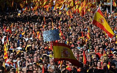 "A protester holds a sign reading ""Now yes, yes, we will vote for real"" amid a wave of Spanish flags during a pro-unity demonstration in Barcelona on October 29, 2017. (AFP PHOTO / LLUIS GENE)"