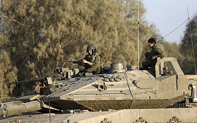 Illustrative: Israeli soldiers sit on a tank close to the Israeli border with the Gaza Strip on October 30, 2017, near Kibbutz Kissufim in southern Israel. (AFP PHOTO/MENAHEM KAHANA)