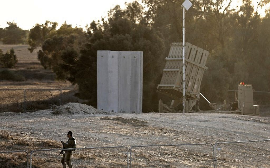 Illustrative: An Israeli soldier stands guard next to Israel's Iron Dome defense system, designed to intercept and destroy incoming short-range rockets and artillery shells, deployed close to the Israeli border with the Gaza Strip, near Kibbutz Kissufim in southern Israel, on October 30, 2017. (AFP Photo/Menahem Kahana)
