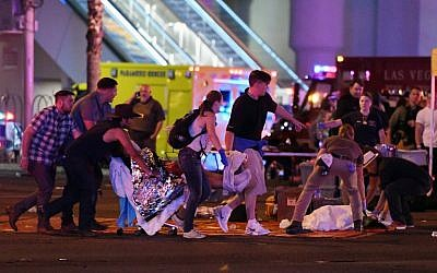 An injured person is tended to at the intersection of Tropicana Avenue and Las Vegas Boulevard after a mass shooting at a country music festival nearby on October 2, 2017 in Las Vegas, Nevada. (Ethan Miller/Getty Images/AFP)