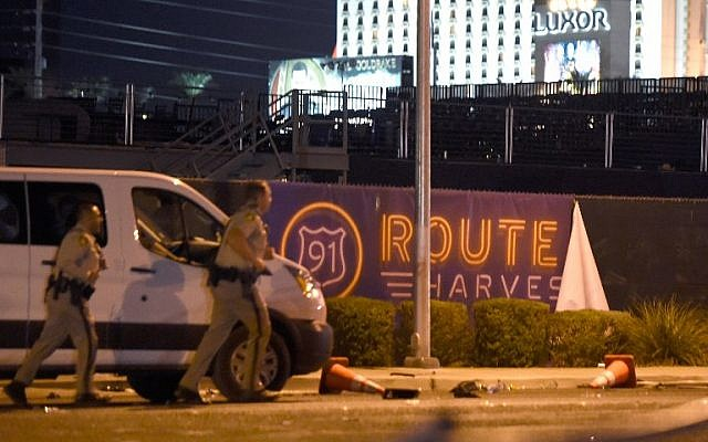 Las Vegas police run by a banner for the Route 91 Harvest country music festival grounds, after a gunman opened fire on the crowd, on October 2, 2017, in Las Vegas, Nevada. (David Becker/Getty Images/AFP)