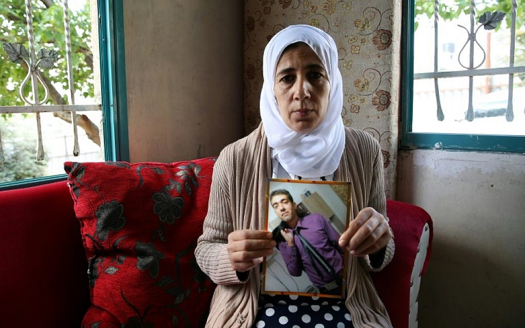Manal al-Sayed holds up a picture of her son, Hisham, who is believed to be held captive in Gaza by the Hamas terrorist group, in 2016. (Yoav Lemmer/AFP)