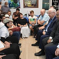President Reuven Rivlin (3rd-R) visits the family of Reuven Schmerling, who was murdered in a terror attack, as it sits shiva, on October 15, 2017. (Mark Neyman/GPO)