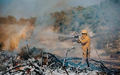 An Israeli firefighter puts out a blaze as part of an international natural disaster preparedness exercise in central Israel on October 24, 2017. (Fire and Rescue Authority)