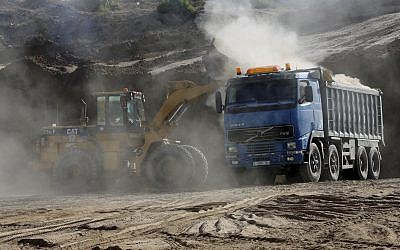 In this Tuesday, Sept. 26, 2017 photo, a bulldozer removes sand at Tel Es-Sakan hill, south of Gaza City. Palestinian and French archaeologists began excavating Gaza's earliest archaeological site nearly 20 years ago; unearthing what they believe is a rare 4,500-year-old Bronze Age settlement.  (AP Photo/Adel Hana)