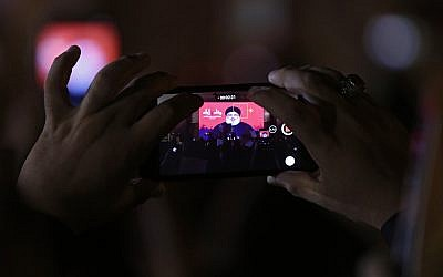 Hezbollah leader Sheik Hassan Nasrallah is displayed on a cellphone as he delivers a message via video link, during the ninth of Ashura, a 10-day ritual commemorating the death of Imam Hussein, in a southern suburb of Beirut, Lebanon, September 30, 2017.  (AP/Hassan Ammar)