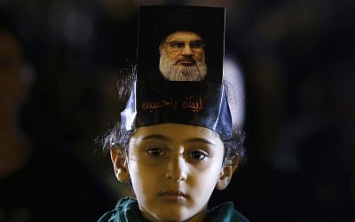 A Hezbollah supporter listens to Hezbollah leader Sheik Hassan Nasrallah, pictured, as he delivers a message via video link, during the ninth of Ashura, a 10-day ritual commemorating the death of Imam Hussein, in a southern suburb of Beirut, Lebanon, Saturday, Sept. 30, 2017 (AP Photo/Hassan Ammar)