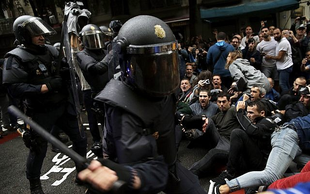 Spanish National Police try to dislodge pro-referendum supporters sitting down on a street in Barcelona, October 1, 2017. (AP/Manu Fernandez)