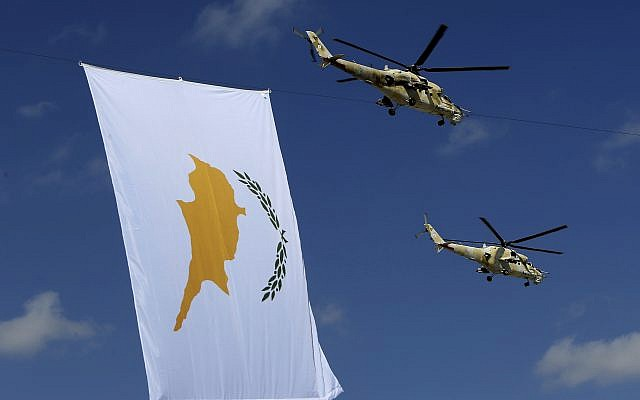 Russian-made military helicopters of the Cypriot air force fly by a Cyprus flag during a military parade marking 57th anniversary of independence, in Nicosia, in the divided island of Cyprus, October 1, 2017. (AP/Petros Karadjias)