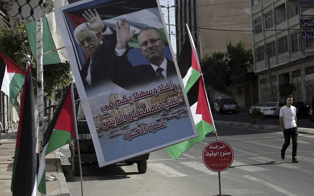 A poster of Palestinian Authority President Mahmoud Abbas and PA Prime Minister Rami Hamdallah hangs on a street in Gaza City, October 1, 2017 (AP Photo/Khalil Hamra)