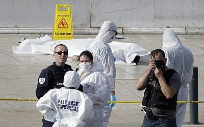 Investigative police officers work by a body under a white sheet outside Marseille's main train station Sunday, Oct. 1, 2017 in Marseille, southern France. A man with a knife attacked people at the main train station, killing two women before soldiers fatally shot him, officials said. (AP Photo/Claude Paris)