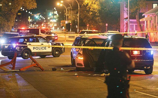 Police investigate the scene where a car crashed into a roadblock in Edmonton Alta, September 30, 2017. (Jason Franson/The Canadian Press via AP)