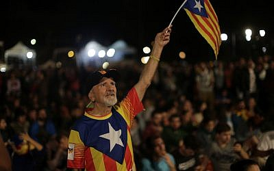 A man waves a ''estelada'' or Catalonia independence flag during a gathering at Plaza Catalonia in Barcelona, Spain, Sunday evening, 1 October 2017. (AP Photo/Emilio Morenatti)