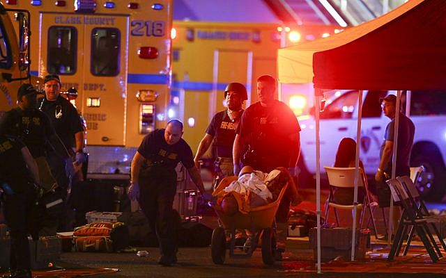 A wounded person is walked in on a wheelbarrow as Las Vegas police respond during an active shooter situation on the Las Vegas Strip in Las Vegas  October 1, 2017. (Chase Stevens/Las Vegas Review-Journal via AP)