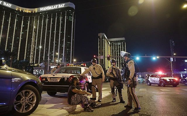 Police officers stand at the scene of a shooting near the Mandalay Bay resort and casino on the Las Vegas Strip, October 1, 2017, in Las Vegas. (AP Photo/John Locher)