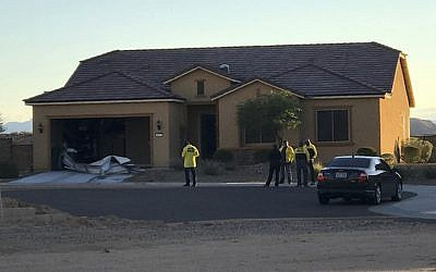 In this photo provided by the Mesquite, Nevada, police department, officers stand outside the home of Stephen Paddock on Monday, October 2, 2017, in Mesquite. Police identified Paddock as the gunman at a music festival Sunday evening. (Mesquite Police via AP)