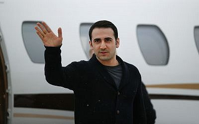 In this Jan. 21, 2016, file photo, Amir Hekmati waves after arriving on a private flight at Bishop International Airport in Flint, Michigan. A judge on Monday, Oct. 2, 2017, ordered Iran to pay $63.5 million to Hekmati, a former US Marine from Michigan who was jailed in that country for more than four years. (AP Photo/Paul Sancya, File)