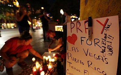 People pause at a memorial on October 3, 2017, set up for victims of the mass shooting in Las Vegas two days before in which 59 were killed and hundreds wounded.  (AP Photo/Gregory Bull)