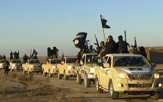 In this undated file photo released by a militant website, which has been verified and is consistent with other AP reporting, jihadists from the Islamic State group hold up their weapons and wave its flags on their vehicles in a convoy to Iraq, in Raqqa, Syria. (Militant website via AP, file)