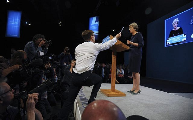 Comedian Simon Brodkin, also known as Lee Nelson, interrupts the Conservative Party Leader and Prime Minister, Theresa May, during her speech at the Conservative Party Conference at Manchester Central, in Manchester, England, Wednesday, Oct. 4, 2017. (AP Photo/Rui Vieira)