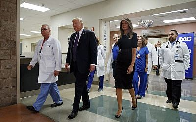 US President Donald Trump and First :ady Melania Trump walk with surgeon Dr. John Fildes, left, at the University Medical Center after meeting with survivors of the mass shooting Wednesday, October 4, 2017, in Las Vegas. (AP Photo/Evan Vucci)