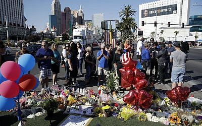People pause at a Las Vegas memorial for the victims of the mass shooting at a concert in the city three days earlier, October 4, 2017. (AP/John Locher)