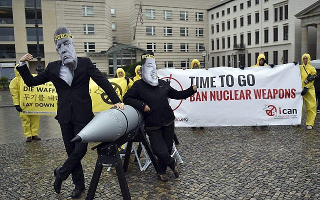 In this file photo from September 13, 2017, activists from the International Campaign to Abolish Nuclear Weapons (ICAN) protest against the conflict between North Korea and the USA with masks of North Korean ruler Kim Jong Un, right, and US president Donald Trump, left, in front of the US embassy in Berlin, Germany. (Britta Pedersen/dpa via AP)