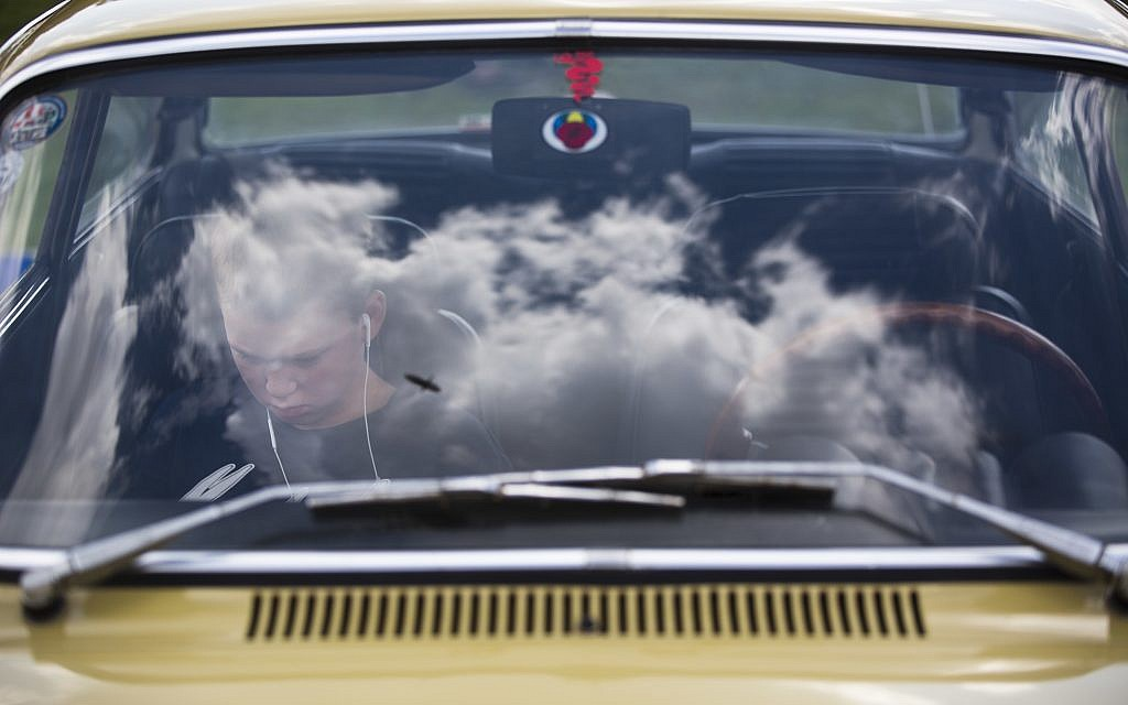 """A youth sits in his grandfather antique car during the 31st annual """"Five Club"""" car collectors' meeting in Ramat Gan, Israel, Friday, Oct. 6, 2017. (AP Photo/Oded Balilty)"""