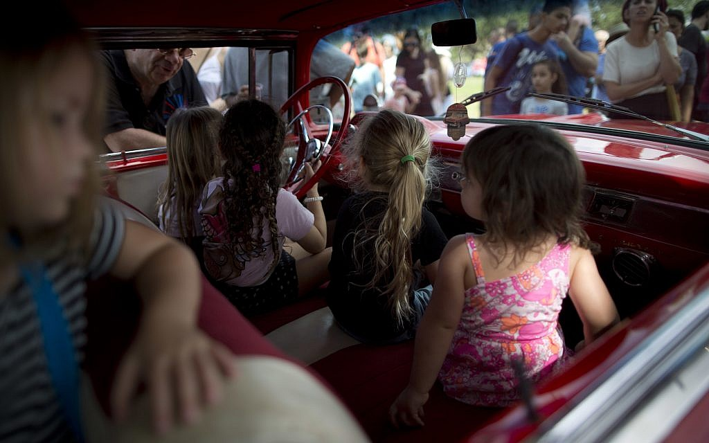 """Children sit in their grandfather's antique car during the 31st annual """"Five Club"""" collectors' car meeting in Ramat Gan, Israel, Friday, Oct. 6, 2017. (AP Photo/Oded Balilty)"""